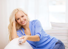Chica joven sonriente con la TV teledirigida en casa Imagenes de archivo
