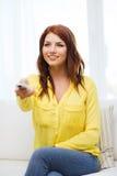 Chica joven sonriente con la TV teledirigida en casa Fotos de archivo libres de regalías