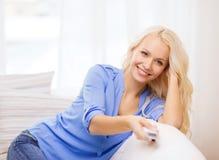 Chica joven sonriente con la TV teledirigida en casa Foto de archivo libre de regalías