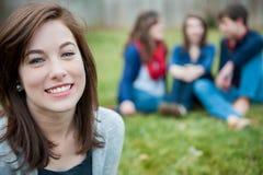 Chica joven sonriente con los amigos en el fondo Imagenes de archivo