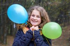 Chica joven sonriente joven con los globos en el fondo del árbol imagen de archivo
