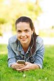 Chica joven sonriente con smartphone y los auriculares Imagenes de archivo
