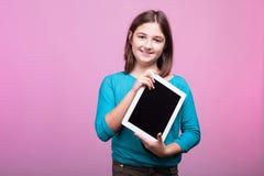 Chica joven sonriente con una tableta digital en manos Fotografía de archivo libre de regalías