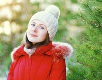 Chica joven sonriente del retrato que lleva una chaqueta y un sombrero rojos en día de invierno Fotos de archivo