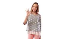 Chica joven sonriente dentuda feliz que muestra el acuerdo con el gestur aceptable Foto de archivo libre de regalías