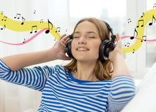 Chica joven sonriente en auriculares en casa Imagen de archivo