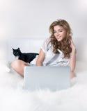 Chica joven sonriente en la cama blanca con el gato negro Foto de archivo
