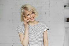 Chica joven sonriente en la luz del día que habla en el teléfono Foto de archivo libre de regalías