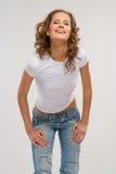 Chica joven sonriente en pantalones vaqueros Imagen de archivo libre de regalías