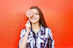 Chica joven sonriente feliz del retrato con la piruleta dulce del caramelo que se divierte Foto de archivo