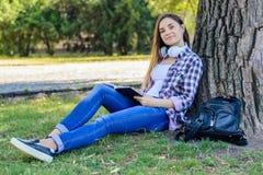 Chica joven sonriente feliz en ropa casual con los auriculares en el ne Imagenes de archivo