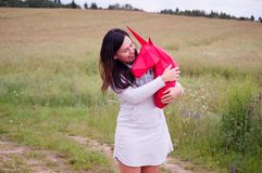 Chica joven sonriente feliz hermosa con unicornio de papel rojo Prado y cielo azul en el backgroundSummer, campo, naturaleza Foto de archivo libre de regalías