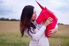 Chica joven sonriente feliz hermosa con unicornio de papel rojo Prado y cielo azul en el backgroundSummer, campo, naturaleza Fotografía de archivo libre de regalías