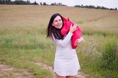 Chica joven sonriente feliz hermosa con unicornio de papel rojo Prado y cielo azul en el backgroundSummer, campo, naturaleza Fotos de archivo libres de regalías