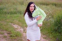 Chica joven sonriente feliz hermosa con unicornio del Libro Verde Prado y cielo azul en el backgroundSummer, campo, naturaleza Foto de archivo