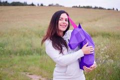 Chica joven sonriente feliz hermosa con unicornio púrpura Prado y cielo azul en el backgroundSummer, campo, naturaleza Fotografía de archivo libre de regalías