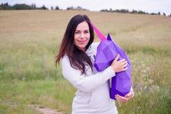 Chica joven sonriente feliz hermosa con unicornio púrpura Prado y cielo azul en el backgroundSummer, campo, naturaleza Foto de archivo