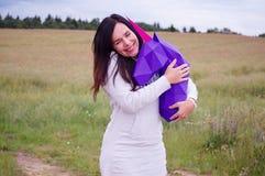 Chica joven sonriente feliz hermosa con unicornio púrpura Prado y cielo azul en el backgroundSummer, campo, naturaleza Imagenes de archivo