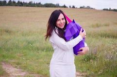 Chica joven sonriente feliz hermosa con unicornio púrpura Prado y cielo azul en el backgroundSummer, campo, naturaleza Fotos de archivo libres de regalías