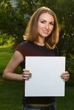 Chica joven sonriente feliz que sostiene el papel en blanco blanco Fotos de archivo
