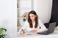 Chica joven sonriente feliz que trabaja en la oficina La muchacha escribe en un cuaderno Retrato del primer de un oficinista Posi imágenes de archivo libres de regalías