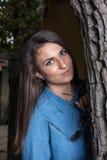 Chica joven sonriente hermosa con los apoyos que se inclinan contra un árbol con el espacio de la copia en fondo negro Foto de archivo libre de regalías