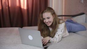 Chica joven sonriente hermosa que usa el ordenador portátil, mintiendo en el sofá almacen de metraje de vídeo
