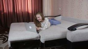 Chica joven sonriente hermosa que usa el ordenador portátil, mintiendo en el sofá almacen de video