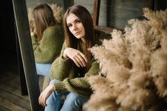 Chica joven sonriente misteriosa en el suéter acogedor hecho punto verde oscuro que se sienta en el piso Foto conceptual del estu fotografía de archivo