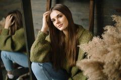 Chica joven sonriente misteriosa en suéter acogedor hecho punto verde oscuro con las gavillas de la composición y del espejo del  fotografía de archivo