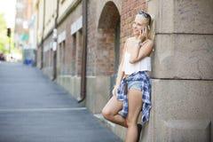 Chica joven sonriente natural que habla en el teléfono Imagen de archivo