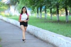 Chica joven sonriente que camina en el paso del parque Foto de archivo