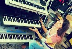 Chica joven sonriente que elige el sintetizador Imagenes de archivo