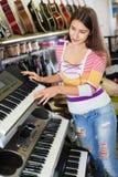 Chica joven sonriente que elige el sintetizador Fotos de archivo libres de regalías