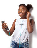 Chica joven sonriente que escucha la música Foto de archivo