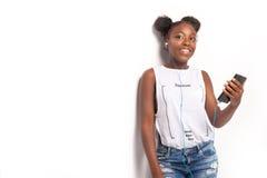 Chica joven sonriente que escucha la música Fotos de archivo libres de regalías