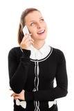 Chica joven sonriente que habla en un teléfono Imagen de archivo