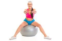 Chica joven sonriente que hace ejercicios en bola de la aptitud Imagenes de archivo