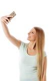 Chica joven sonriente que hace la foto del selfie aislada en un blanco Fotos de archivo