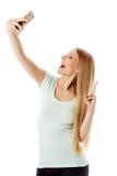 Chica joven sonriente que hace la foto del selfie aislada en un blanco Imagen de archivo
