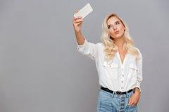 Chica joven sonriente que hace la foto del selfie en smartphone Imágenes de archivo libres de regalías