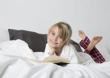 Chica joven sonriente que lee un libro Imagen de archivo
