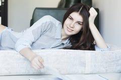 Chica joven sonriente que lee una revista Imagen de archivo