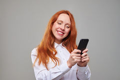 Chica joven sonriente que mecanografía un mensaje de texto en phon móvil Foto de archivo
