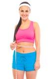 Chica joven sonriente que mide su cintura Imagen de archivo libre de regalías