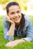 Chica joven sonriente que miente en hierba Fotos de archivo