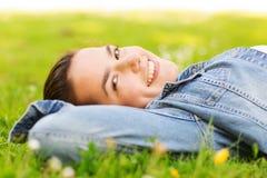 Chica joven sonriente que miente en hierba Foto de archivo
