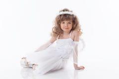 Chica joven sonriente que presenta en traje del ángel Fotos de archivo libres de regalías