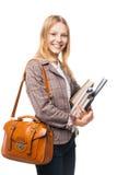 Chica joven sonriente que se coloca con el bolso y los libros Imagenes de archivo