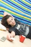 Chica joven sonriente que se relaja en suelo con el telecontrol Fotografía de archivo